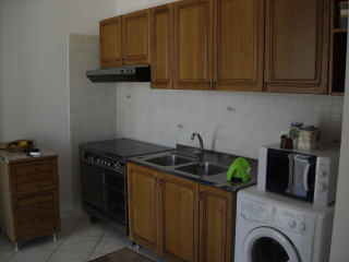 Kitchen with four hotplates, oven, washing machine.