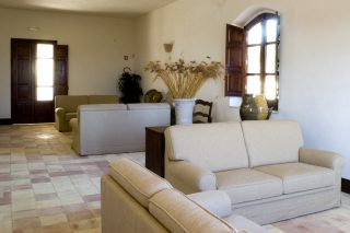 The wide and spacious hall in the Heart of Dionysus, with comfortable sofas and rustic decor with antique furniture